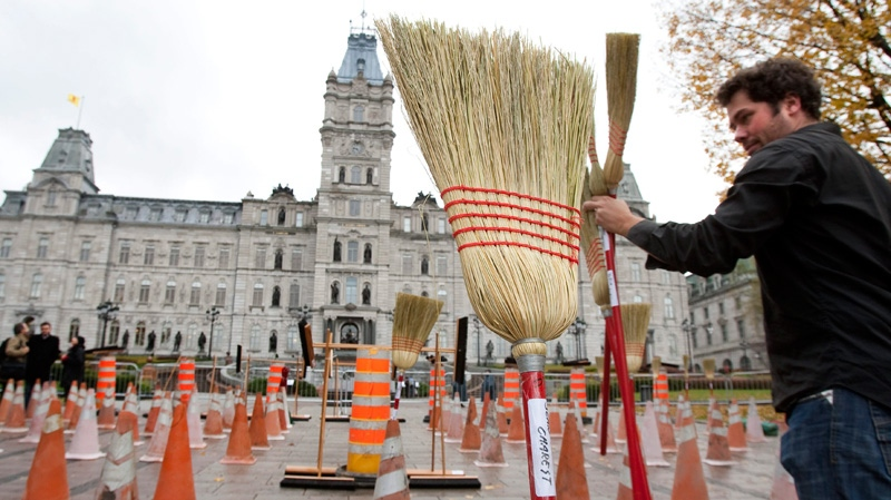 A broom bearing the name of Quebec Premier Jean Charest sits in the middle of the place as Olivier Charest installs brooms on road construction signs, asking for a public inquiry in the construction industry Tuesday, Oct. 18, 2011 at the legislature in Quebec City.  (Jacques Boissinot / THE CANADIAN PRESS)