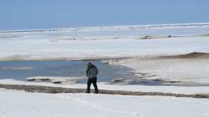 man walks near ice-covered Lake Huron