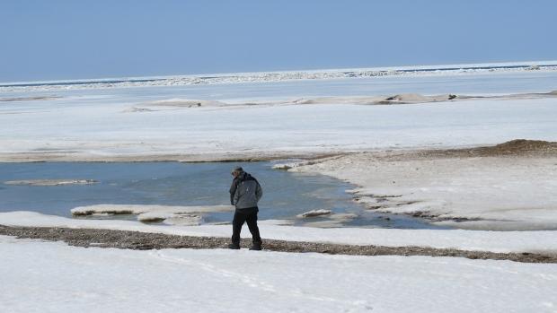 man walks near ice-covered Lake Huron