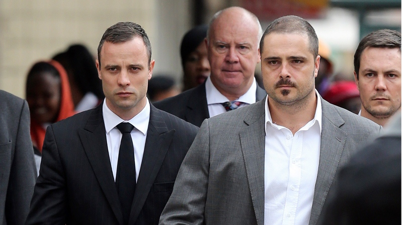 Oscar Pistorius, left, accompanied by relatives walks towards the high court in Pretoria, South Africa, Wednesday, April 9, 2014. (AP / Themba Hadebe)