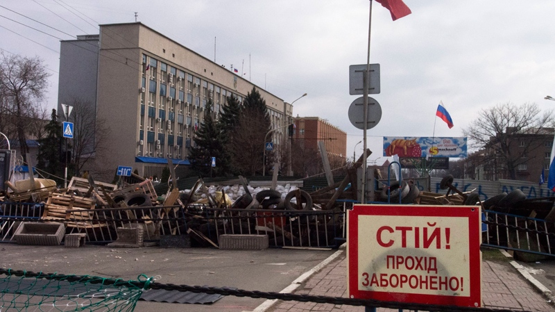 Barricades and Soviet era red and Russian national flags with a poster reading 'Stop, no entrance!' are seen in front of an entrance of the Ukrainian regional office of the Security Service in Luhansk, Ukraine on Wednesday, April 9, 2014. (AP Photo/Igor Golovniov)