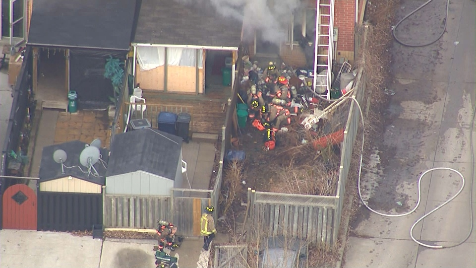 Firefighters gather at the back of a burning townhouse on Perth Avenue on Wednesday, April 9, 2014.