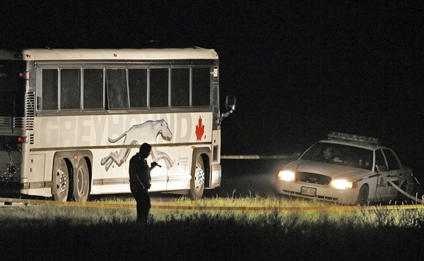 RCMP officers investigate a violent incident that occured on a Greyhound bus about 18 km west of Portage La Prairie, Man. on Thursday, July 31, 2008. (John Woods / THE CANADIAN PRESS)