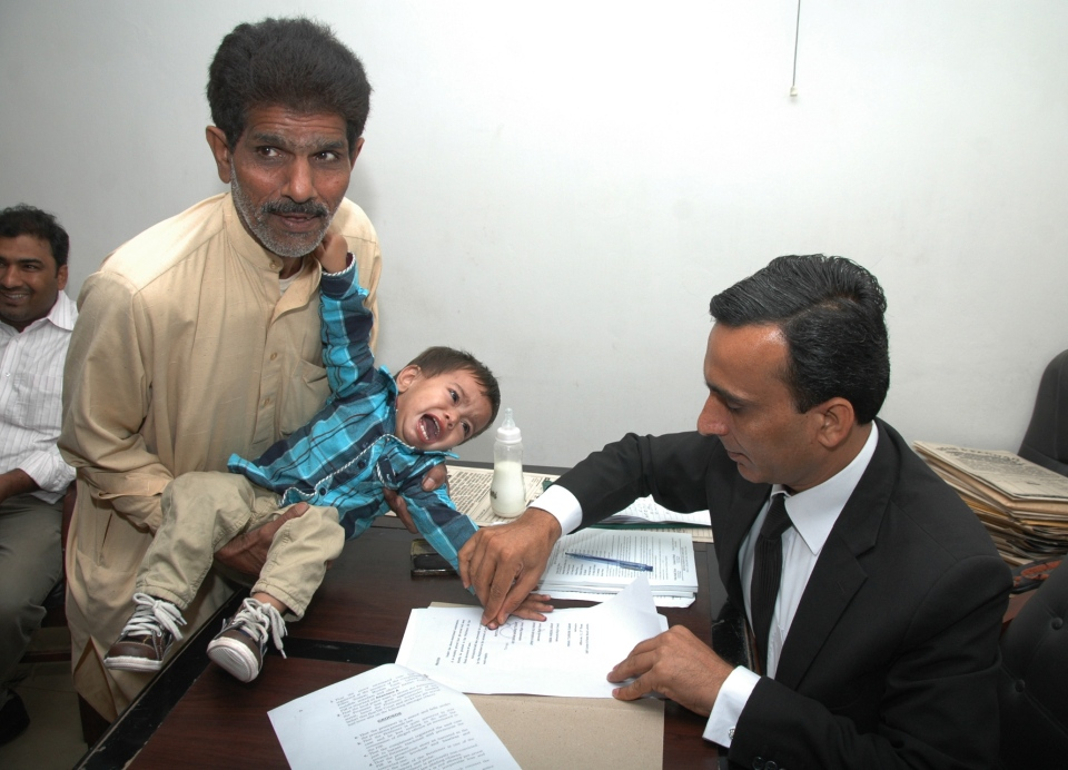 A Pakistani lawyer gets thumb impression of a nine-month-old boy on legal papers for bail in Lahore, Pakistan, on April 3, 2014. He was swept up in an attempted murder investigation that is highlighting the country's dysfunctional criminal justice system. (AP Photo)