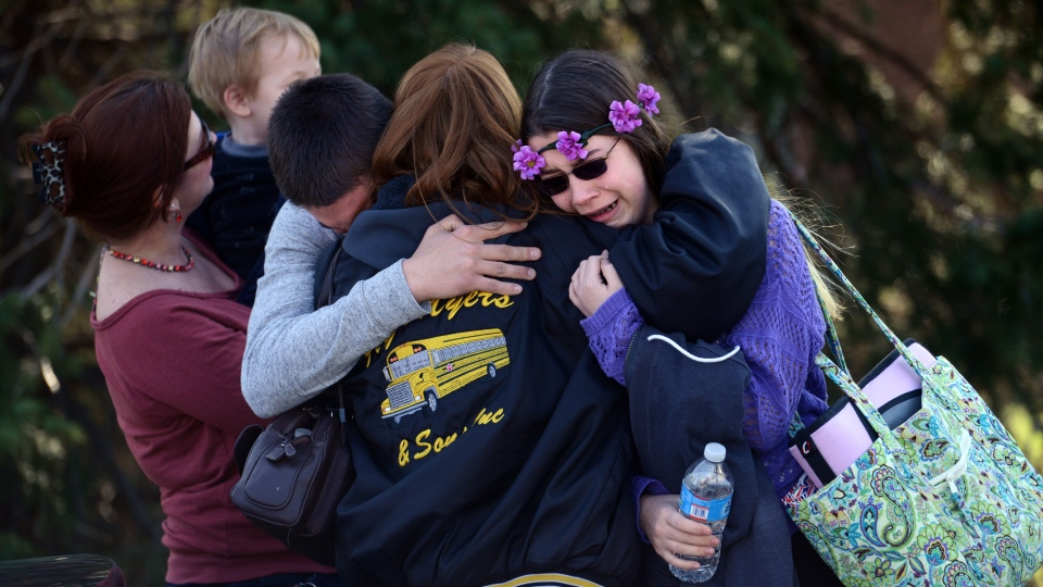 Parents and students embrace along School Road near Franklin Regional High School after more than a dozen students were stabbed by a knife wielding suspect at the school in Murrysville, Pa., near Pittsburgh on Wednesday, April 9, 2014. (Tribune Review, Sean Stipp)