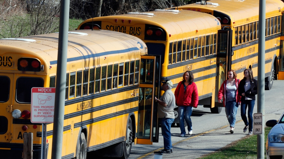 Students walk past a row of buses as they leave the campus of the Franklin Regional School District after more then a dozen students were stabbed by a knife wielding suspect at nearby Franklin Regional High School in Murrysville, Pa., near Pittsburgh on Wednesday, April 9, 2014. (AP / Gene J. Puskar)