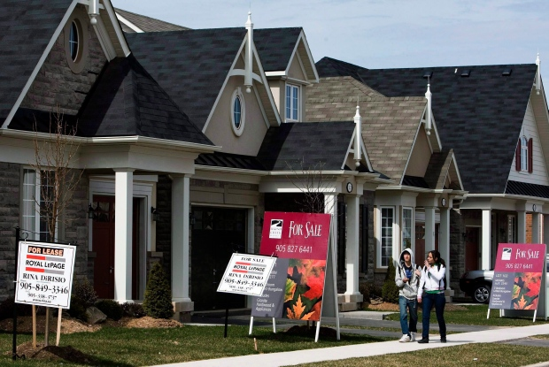 People walk past new homes in Oakville