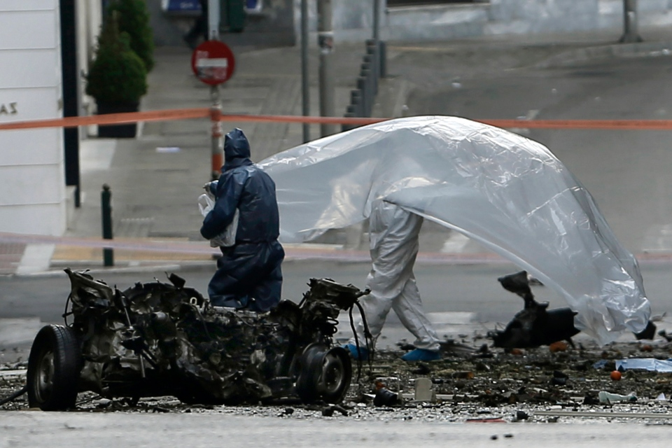 Police bomb disposal experts place plastic sheeting over the remains of a car bomb that exploded in central Athens, Thursday, April 10, 2014. (AP / Petros Giannakouris)