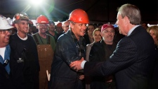 Jim Irving, right, CEO of Irving Shipbuilding, greets workers at the announcement that Halifax Shipyard is getting the $25 billion contract to build 21 Canadian combat ships, in Halifax on Wednesday, Oct. 19, 2011. (Andrew Vaughan / THE CANADIAN PRESS)