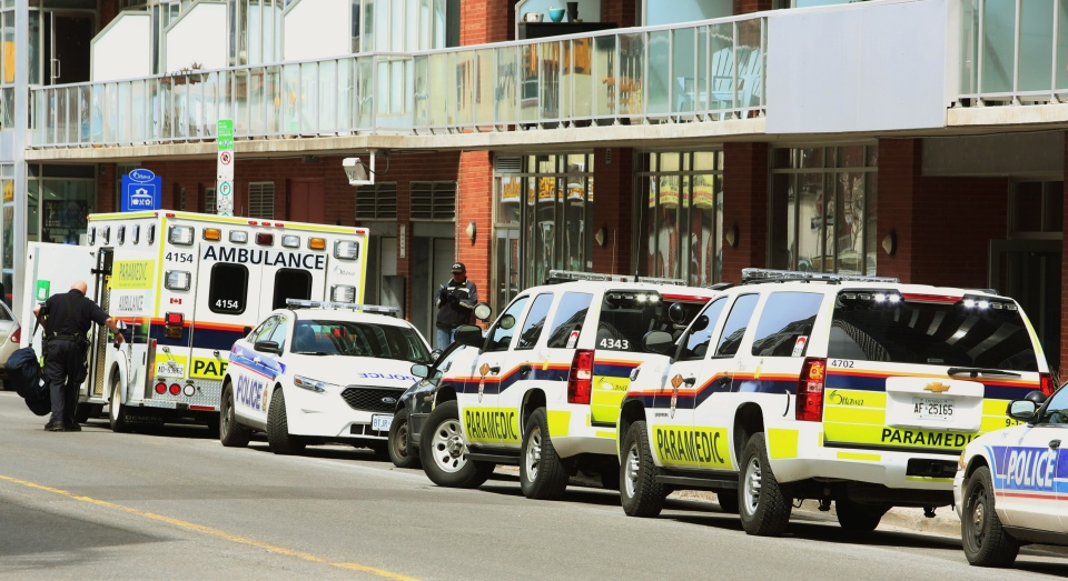 Ambulances and police cars park outside the apartment building were former Finance Minister Jim Flaherty resided in Ottawa Thursday, April 10, 2014. (Fred Chartrand / THE CANADIAN PRESS)