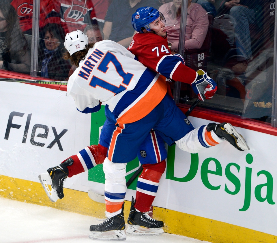 Montreal Canadiens defenceman Alexei Emelin (74) is checked into the boards by New York Islanders left wing Matt Martin (17)during first period NHL action Thursday, April 10, 2014 in Montreal.THE CANADIAN PRESS/Ryan Remiorz