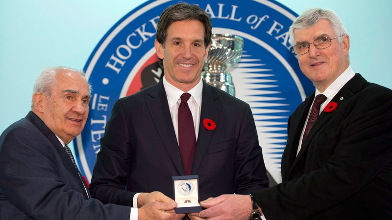 Hockey Hall of Fame inductee Brendan Shanahan is presented with his ring by Chairman Pat Quinn (right) and Chair of the selection committee Jim Gregory at the Hall in Toronto on Friday, Nov. 8, 2013. (Frank Gunn / THE CANADIAN PRESS)