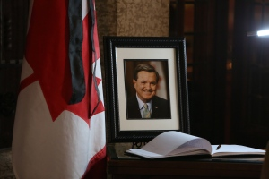 A book of condolences and a photograph of former Finance Minister Jim Flaherty is placed on a table in the lobby of House of Commons on Parliament Hill in Ottawa on Friday, April 11, 2014. Flaherty died suddenly Thursday of an apparent heart attack. He was 64. (Fred Chartrand / THE CANADIAN PRESS)