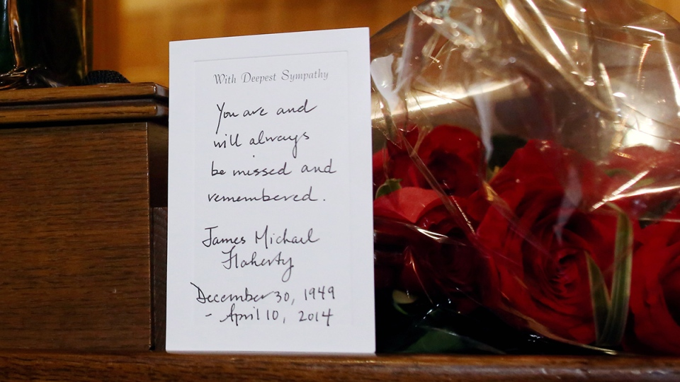 Flowers and a card of sympathy are placed in honour of former Finance Minister Jim Flaherty on a desk in the House of Commons on Parliament Hill in Ottawa on Friday, April 11, 2014. (Fred Chartrand / THE CANADIAN PRESS)