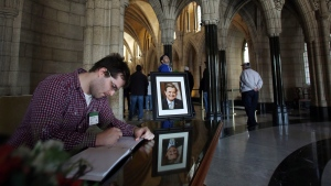 Ryan Tenta, of Vancouver, signs a public book of condolences in honour of former Finance Minister Jim Flaherty in the rotunda of the Hall of Honor on Parliament Hill in Ottawa on Friday, April 11, 2014. (Fred Chartrand / THE CANADIAN PRESS)