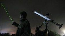 An astronomer uses a laser pointer to show the radiant of the Orionids at an observatory east of the Bulgarian capital Sofia, in this Oct. 20, 2009 file photo. (AP Photo/Petar Petrov)