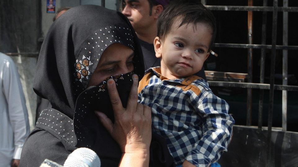 An unidentified family member holds a nine-month-old boy, trying to avoid media as they leave after the boy's court appearance in Lahore, Pakistan, Saturday, April 12, 2014. (AP / K.M. Chaudary)