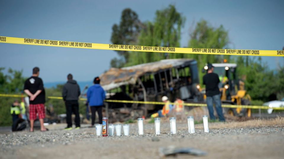 Candles and flowers are seen at a make-shift memorial for the victims of a multi-vehicle accident that included a tour bus and a FedEx truck near Orland, Calif. on Friday, April 11, 2014. (The Sacramento Bee / Hector Amezcua)