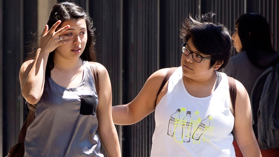Students Mary Jeanne Arriaga, left, and Heidi Mendez, react after learning about the death of student Adrian Castro, as they leave El Monte High School in El Monte, Calif., Friday, April 11, 2014. (AP / Damian Dovarganes)