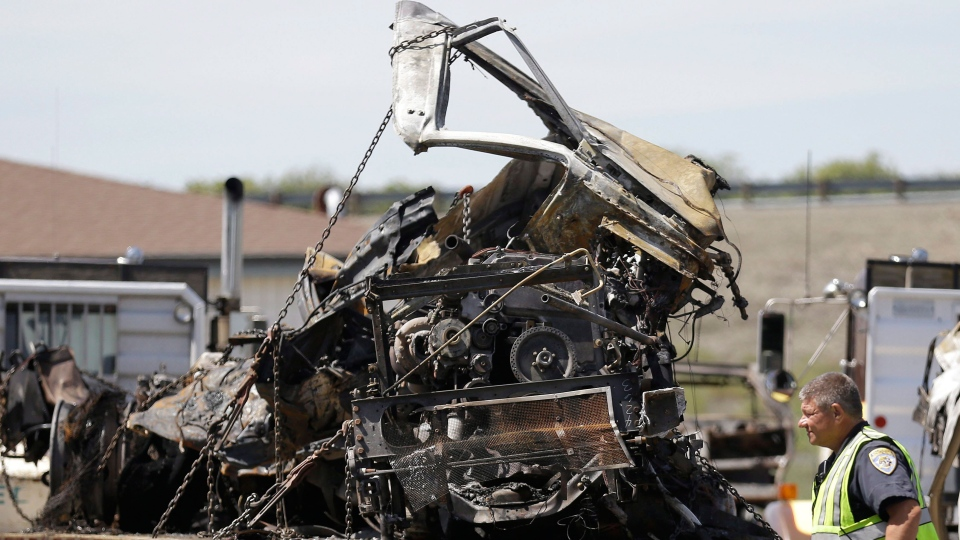 A California Highway Patrol officer walks past the demolished cab of a FedEx truck at a CalTrans maintenance station in Willows, Calif., Friday, April 11, 2014. (AP / Jeff Chiu)