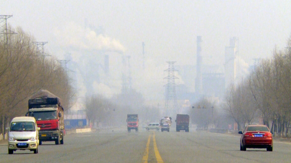 Cars drive in a thick blanket of smog created by China's rapidly expanding industrial economy.