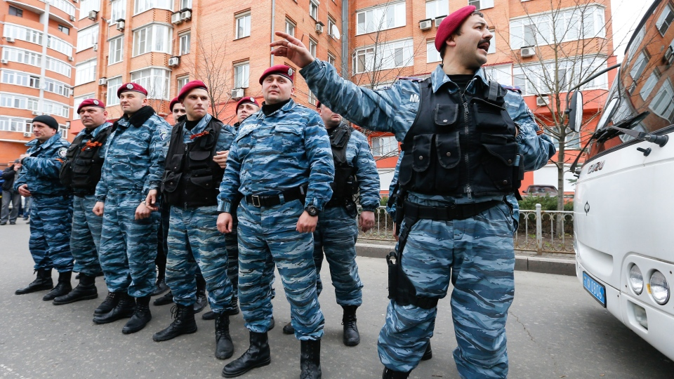 A group of Ukraine's now-defunct riot police officers stand in their uniforms, as they guard in front of regional police building in Donetsk, Ukraine, Saturday, April 12, 2014. (AP / Andrey Basevich)