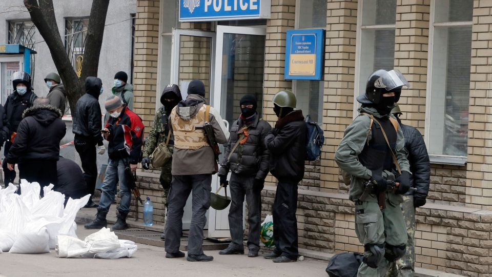 Armed pro-Russian activists occupying the police station in the eastern Ukraine town of Slovyansk carry riot shields on in Slovyansk, Saturday, April 12, 2014. (AP / Efrem Lukatsky)