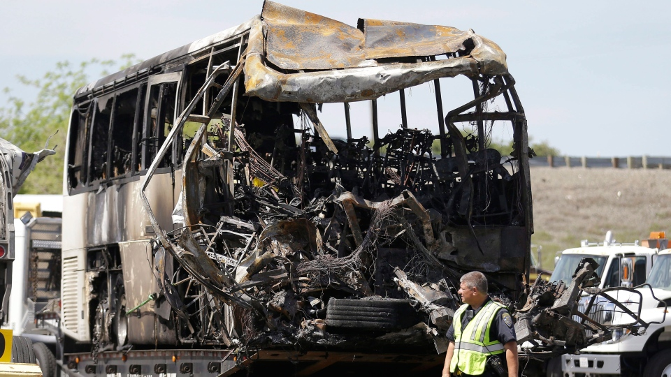 A California Highway Patrol officer walks past the charred remains of a tour bus at a CalTrans maintenance station in Willows, Calif., Friday, April 11, 2014. (AP / Jeff Chiu)