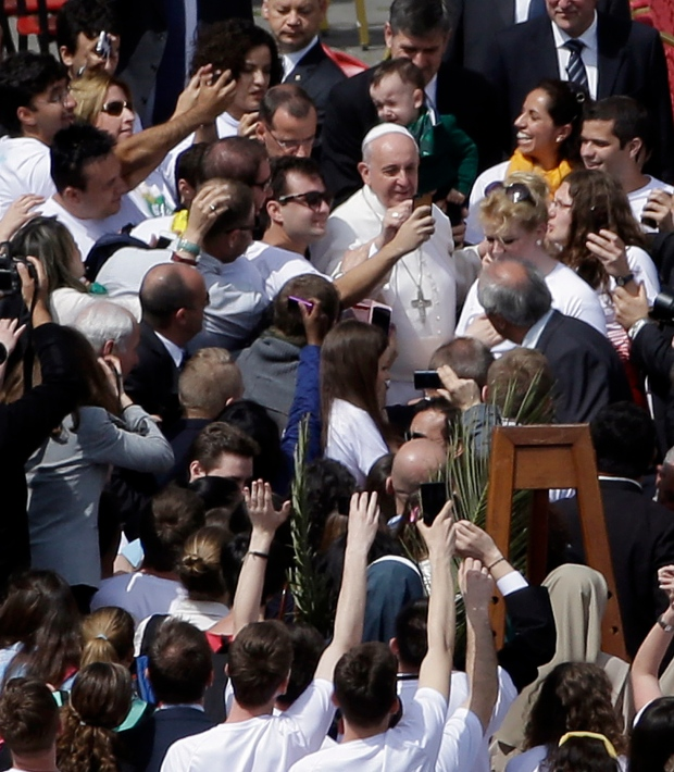 Pope Francis poses for pictures with faithful