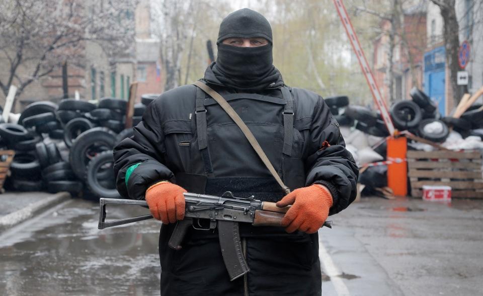 A pro-Russian gunman stands guard at a seized police station in the eastern Ukraine town of Slovyansk on Sunday, April 13, 2014. (AP Photo/Efrem Lukatsky)