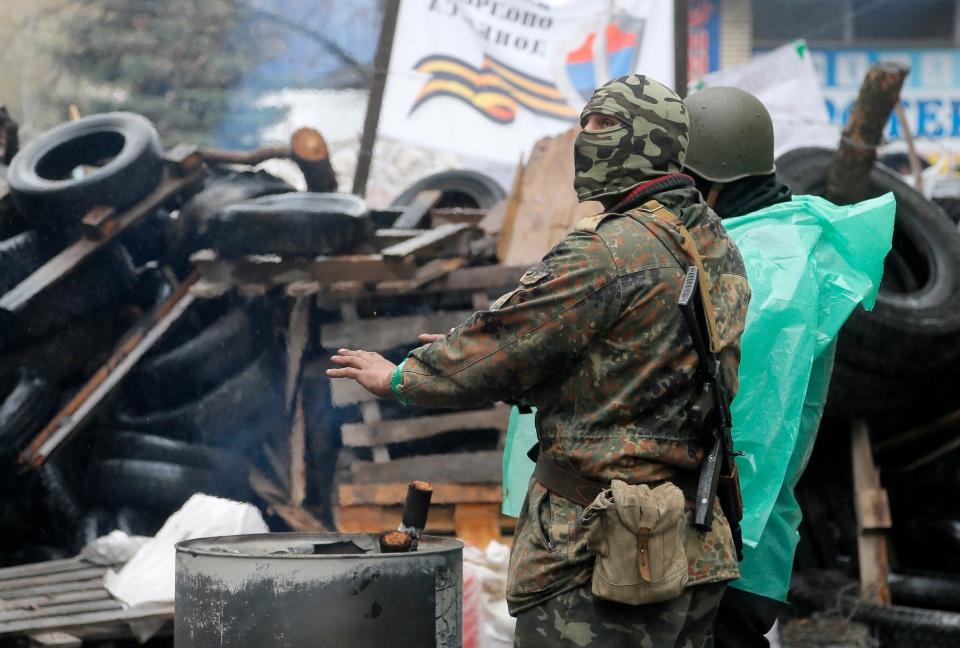 A pro-Russian gunman warms himself next to a bonfire as he guards a seized police station in the eastern Ukrainian town of Slovyansk on Sunday, April 13, 2014.  (AP / Efrem Lukatsky)