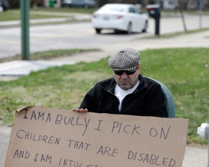 Edmond Aviv sits on a street corner holding a sign Sunday, April 13, 2014, in South Euclid, Ohio declaring he's a bully, a requirement of his sentence because he was accused of harassing a neighbor and her disabled children for the past 15 years. (AP Photo/Tony Dejak)