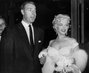 In this June 2, 1955 file photo, actress Marilyn Monroe, right, in a glamorous evening gown, with Joe DiMaggio, arrives at the theater. (AP / File)