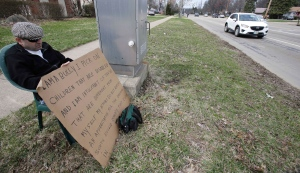 Edmond Aviv sits on a street corner holding a sign in South Euclid, Ohio, Sunday, April 13, 2014. (AP  / Tony Dejak)
