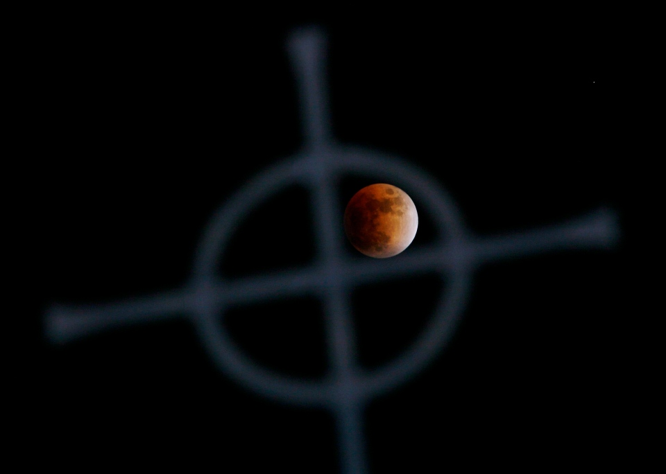 A lunar eclipse is framed in a church's steeple cross just west of Ottawa on Feb. 20, 2008. (Sean Kilpatrick/THE CANADIAN PRESS)