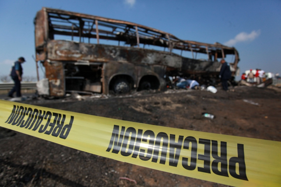 Caution tape creates a perimeter around a passenger bus that slammed into a broken-down truck and burst into flames near the town of Ciudad Isla in the Gulf state of Veracruz, Mexico, Sunday, April 13, 2014. (AP / Felix Marquez)