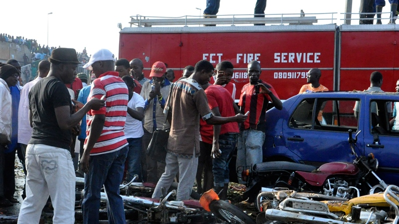 People gather at the site of a blast at the Nyanya Motor Park, about 16 kilometres from the centre of Abuja, Nigeria, Monday, April 14, 2014. (AP / Gbemiga Olamikan)