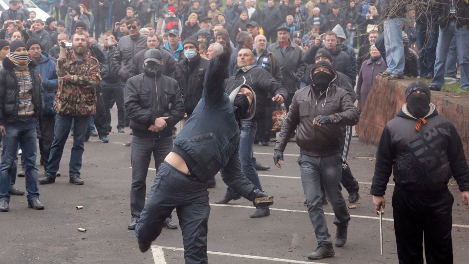 Pro-Russian men throw stones during the mass storming of a police station in the eastern Ukrainian town of Horlivka Monday, April 14, 2014. (AP / Efrem Lukatsky)
