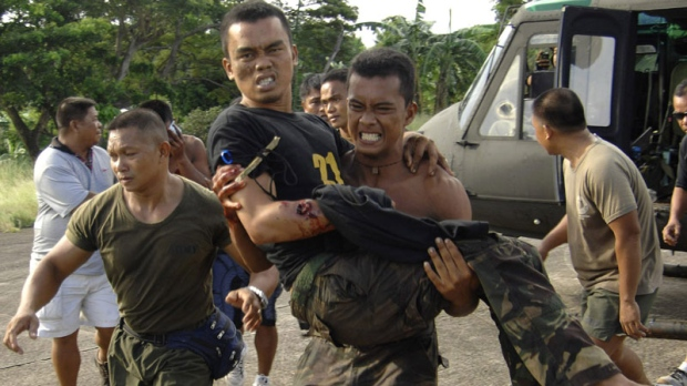A soldier carries a wounded trooper from Basilan province as they land at the southern port city of Zamboanga, Philippines Tuesday, Oct. 18, 2011. Philippine troops are battling Muslim guerrillas in fierce fighting in volatile Basilan province that has killed at least 15 combatants. (AP Photo)