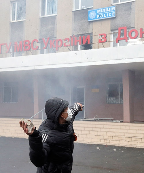 A pro-Russian man throws a stone during the mass storming of a police station in the eastern Ukrainian town of Horlivka on Monday, April 14, 2014. (AP/ Efrem Lukatsky)