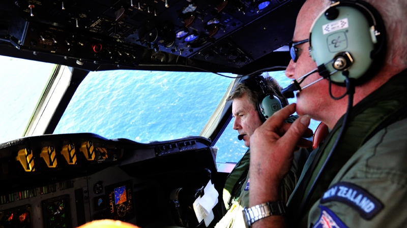 Royal New Zealand Air Force (RNZAF) co-pilot squadron leader Brett McKenzie, left, and Flight Engineer Trent Wyatt sit in the cockpit aboard a P-3 Orion on route to search over the southern Indian Ocean looking for missing Malaysia Airlines flight MH370 Friday, April 11, 2014. (AP / Richard Polden)