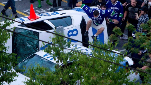 A Vancouver Canucks fan jumps from a police car that was overturned by rioters following the Vancouver Canucks defeat by the Boston Bruins in the NHL Stanley Cup Final in Vancouver, in this file photo taken June 15, 2011. (Darryl Dyck / THE CANADIAN PRESS)