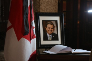 A book of condolences and a photograph of former Finance Minister Jim Flaherty is placed on a table in the lobby of House of Commons on Parliament Hill in Ottawa on Friday, April 11, 2014. (Fred Chartrand / THE CANADIAN PRESS)