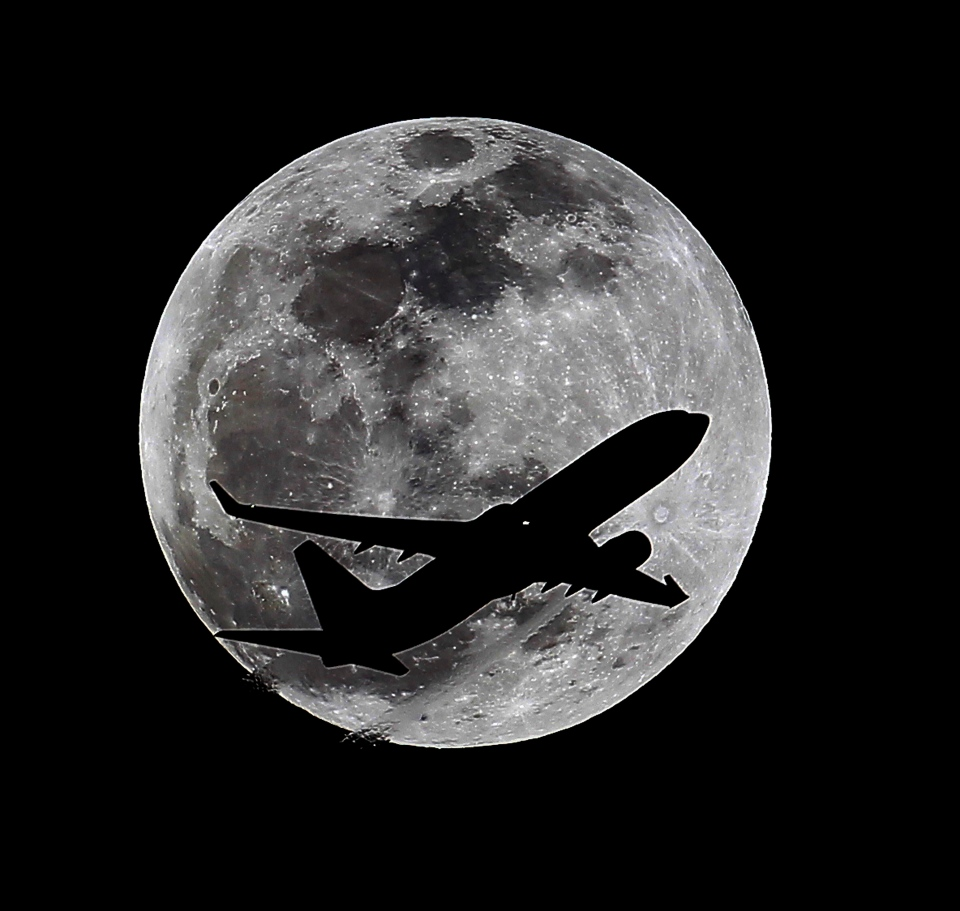 An airliner crosses the moon's path, Monday, April 14, 2014, above Whittier, Calif., approximately one hour before a total lunar eclipse. (AP / Nick Ut)