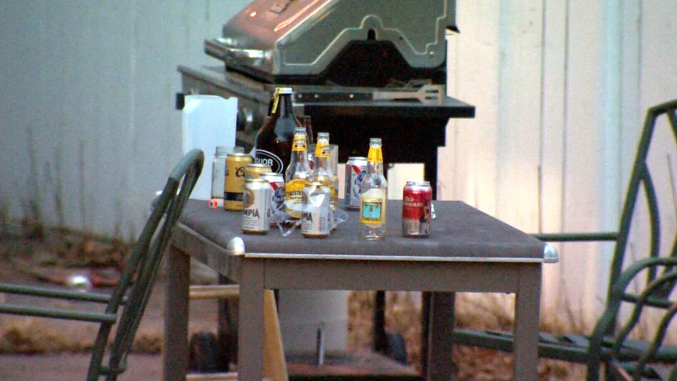 Empty beer bottles sit on a table in a backyard where a house party was held before five people were stabbed to death in Calgary, Tuesday, April 15, 2014.