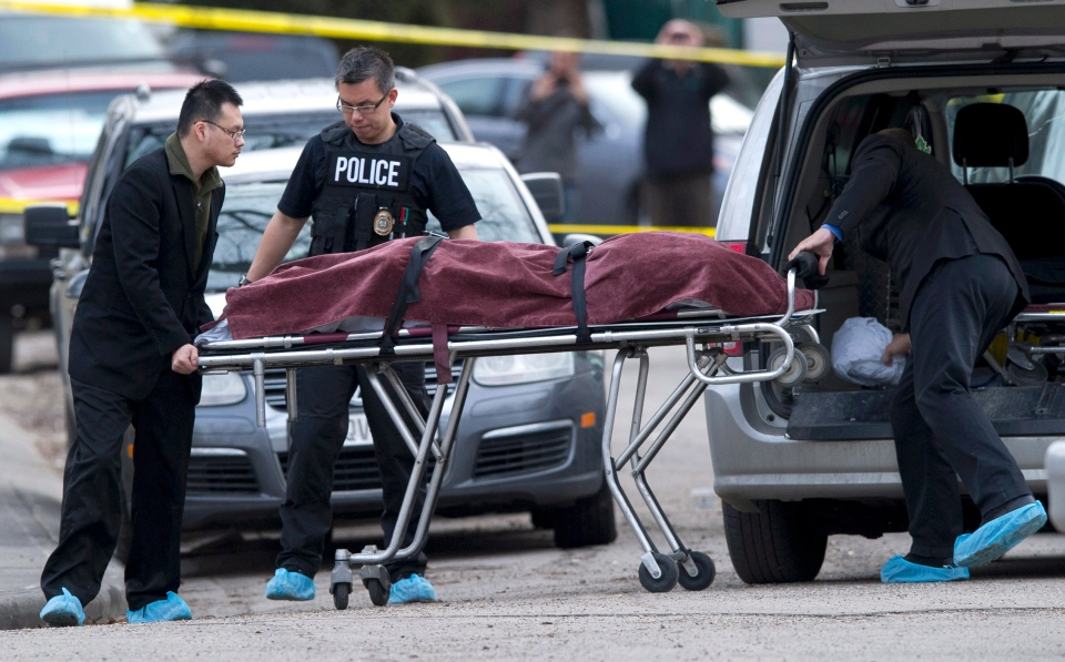 Police remove a body from the scene of a multiple fatal stabbing in northwest Calgary, Tuesday, April 15, 2014. (Larry MacDougal / THE CANADIAN PRESS)