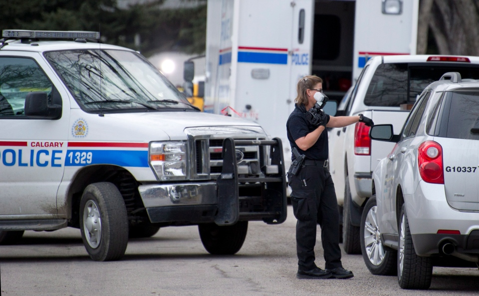 Police investigator at the scene of a multiple fatal stabbing in northwest Calgary, Alberta on Tuesday, April 15, 2014.  (Larry MacDougal / THE CANADIAN PRESS)