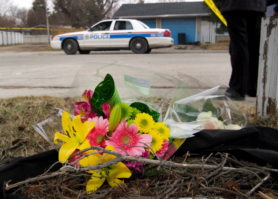 Makeshift memorial at police tape line near the scene of a multiple fatal stabbing in northwest Calgary, Alberta on Tuesday, April 15, 2014.  (Larry MacDougal /  THE CANADIAN PRESS)