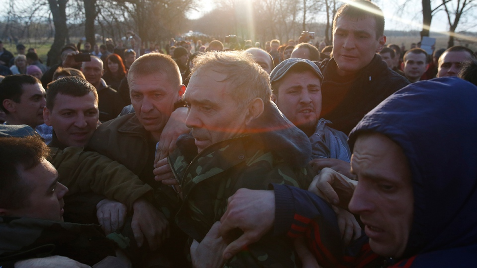 Pro-Russian activists attack Ukraine's security services anti-terrorist unit chief, Gen. Vasyl Krutov, centre, after he spoke outside Kramatorsk airport, eastern Ukraine, Tuesday, April 15, 2014. (AP / Sergei Grits)