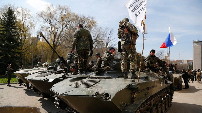 Combat vehicles with a Russian flag, a Donetsk Republic flag and gunmen on top are parked in downtown of Slovyansk on Wednesday, April 16, 2014. (AP / Sergei Grits)